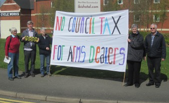 "Campaigners holding banner saying ""No Council Tax for arms dealers"""