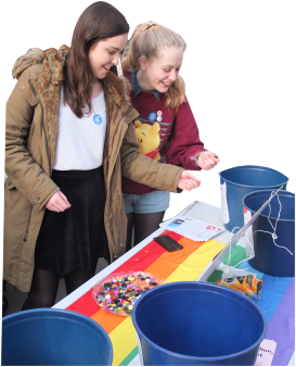 Two young people drop buttons into buckets to vote for a safer world